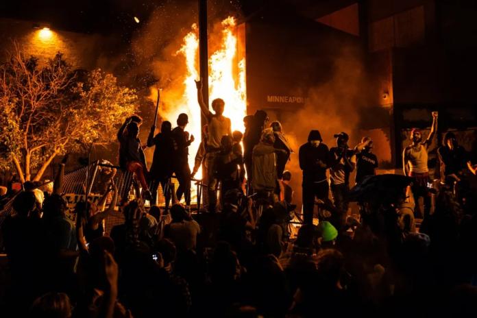 Демонстранты на фоне горящего отделения полиции Миннеаполиса. 25 мая 2020 года его сотрудники при задержании убили 46-летнего афроамериканца Джорджа Флойда, после чего в городе начались массовые беспорядки. Миннеаполис, штат Миннесота, 28 мая 2020 года
