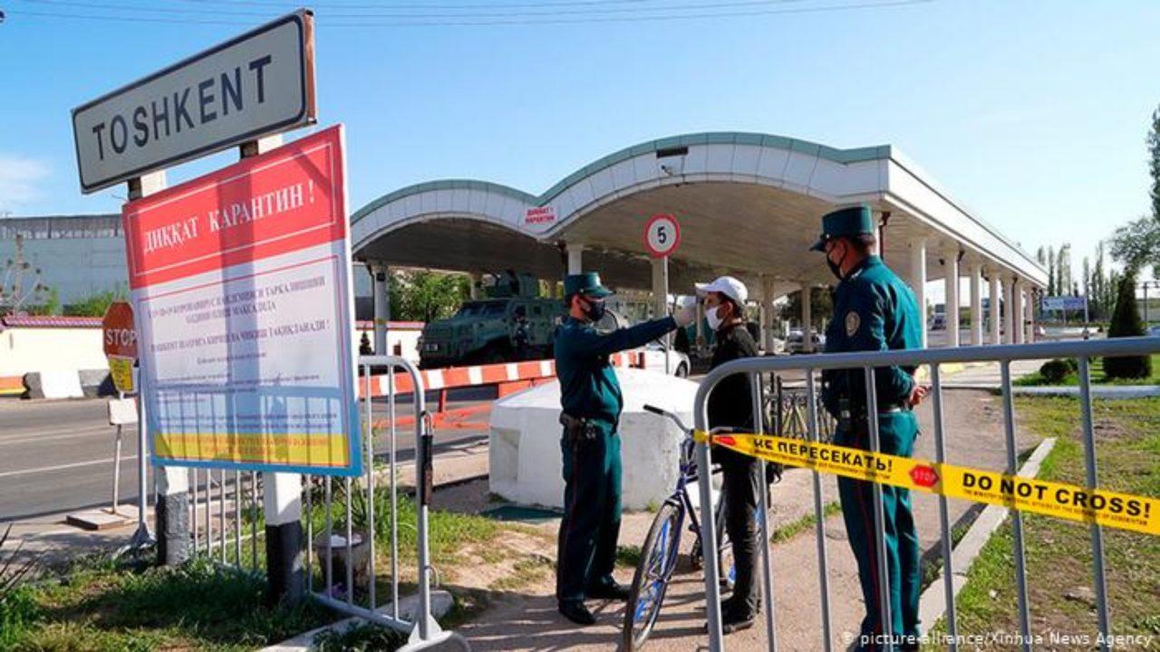 Сотрудники милиции проверяют температуру у прохожего на посту между Ташкентом и Ташкентской областью